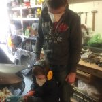 Thomas sanding the hatch trim down with the Fein multitool sporting his PPE 1